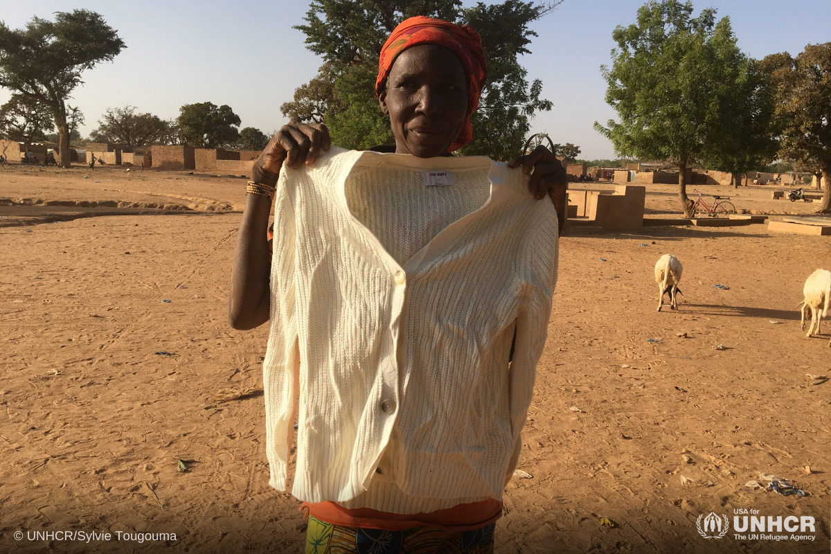 Zonabo, a refugee woman from Burkina Faso, receives a shirt from Gap in-kind donation